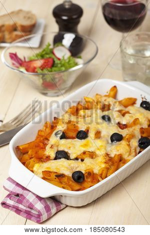 rigatoni pasta with olives and wine on wood