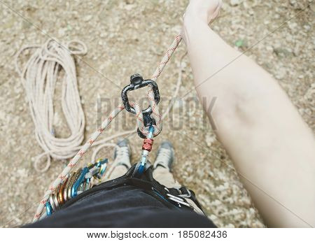Unrecognizable female climber wearing in safety harness standing with figure eight and rope point of view.
