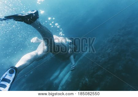 Young woman free diver in flippers with mask and snorkel swimming underwater to seaweed rear view.