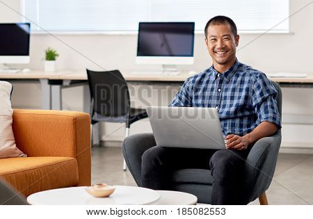 Portrait of a smiling young Asian designer working online with a laptop while sitting alone on a chair in a large modern office