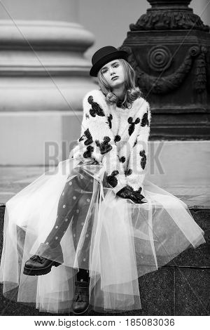 Woman in black and white clothes. Stylish retro urban girl trendy new age look. Accessories hat and Gloves. Fashion model posing in city stree. Photography portfolio.