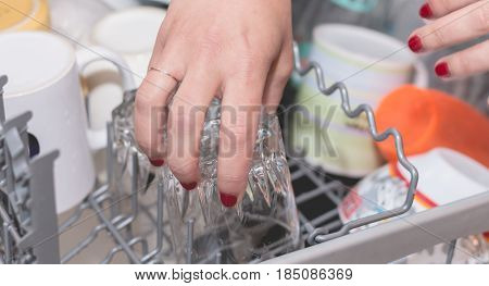 Close-up Of A Hand Filling A Dishwasher
