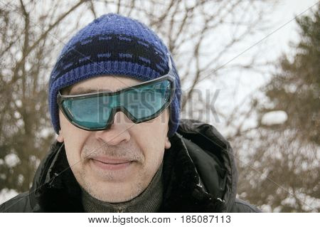 Askewed ski glasses on a face of a funny looking man