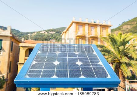 A small solar panel powering a parking ticket vending machine in a parking lot in Bonassola, Cinque Terre, Italy.