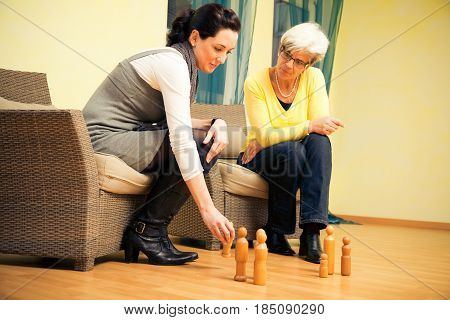 systemic therapy works with different, practically oriented methods. in this shot, the patient or client uses wooden figurines to visually represent a context or situation within a group of people, e.g. family, company, friends, while the therapist or cou
