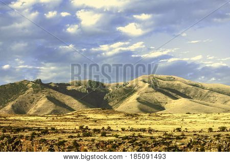 Foothills of the mountains Ara with the impending by the sky thunderclouds clouds in an evening autumn day