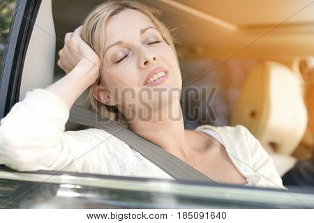 Blond woman relaxing in car passenger seat