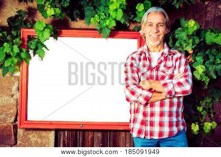 winemaker standing by a billboard. billboard is pure white so you can easily add your own content.