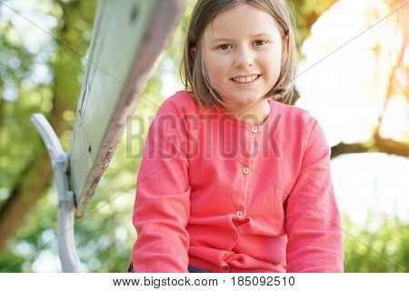 Portrait of 8-year-old girl sitting on bench in park