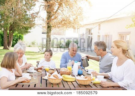 Family of 6 having breakfast together outside the house