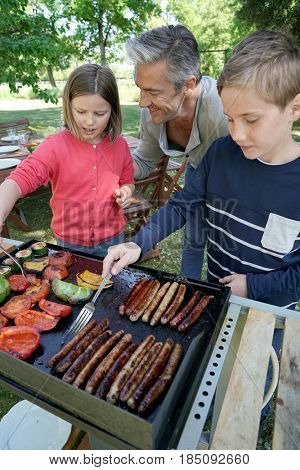 Father with kids preparing barbecue for family lunch