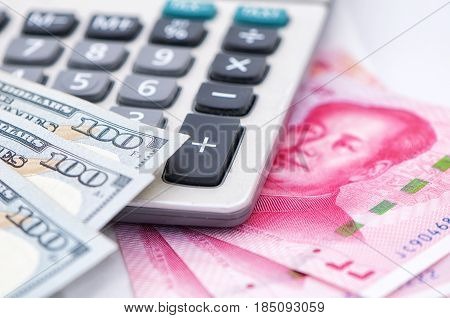 One hundred U.S. dollars and 100 Renminbi bills on top of a calculator.