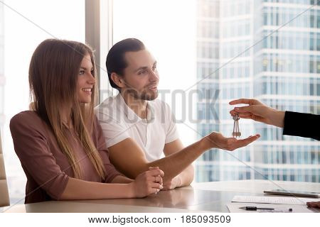 A hand of female real estate agent giving keys to own first apartment to couple, finishing real estate deal at the agency office with smiling family, renters or buyers happy to get access to new home