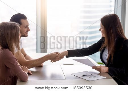 Young smiling couple visiting real estate agency shaking hands with realtor, purchasing renting flat or house, apartment buyers making deal, family couple and broker handshaking after signing papers poster