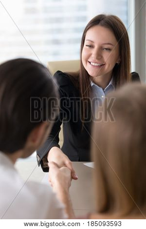 Beautiful friendly real estate agent and client handshaking at office, nice to meet you, businesswoman meeting partners, shaking hands over a table, making deal or partnership, business acquaintance