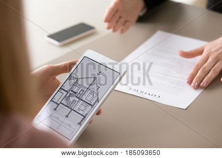 Real estate agency clients holding tablet, looking at architectural plan of dream house, considering mortgage, loan for buying suburban housing. Renters choosing accommodation to lease or rent