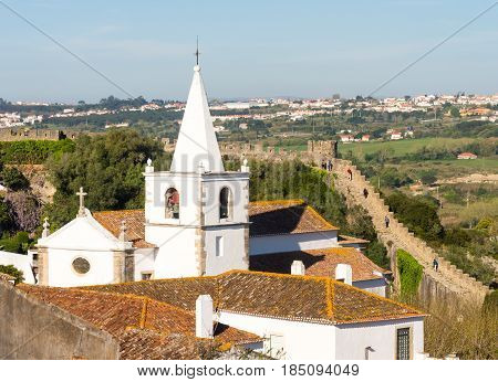 OBIDOS PORTUGAL - APRIL 03 2017: Tower of Santa Maria church and castle wall in Obidos Portugal.