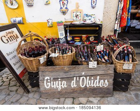 OBIDOS PORTUGAL - APRIL 03 2017: Gift store selling Ginja de Obidos traditional regional cherry liquor.