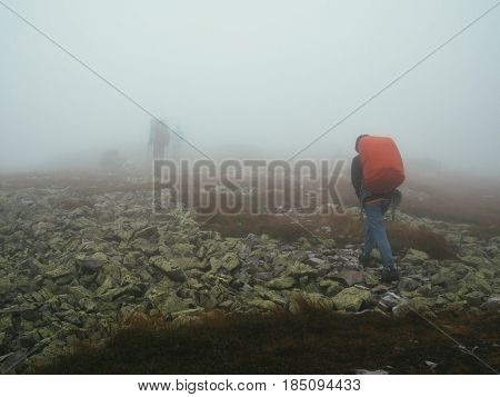Tourists travelers with backpacks walking through the rocks in thick mist of milk. Poor visibility and easy to get lost.