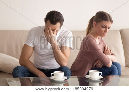 Family couple sitting on the couch not talking after argument, young husband is tired of constant quarrelling and touching his forehead, offended woman turned her back to boyfriend with arms across