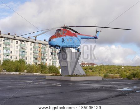 Old helicopter on pedestal in northern russia town with tundra landscape at background