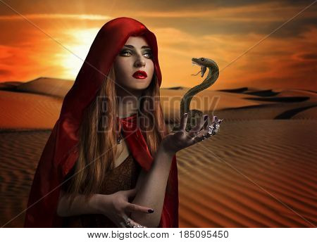 Woman with snake in the desert. Pretty woman in red cloak holding a snake standing in the desert photo.