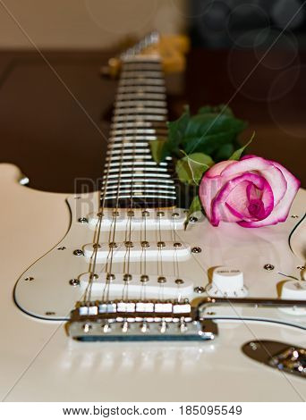 White guitar with pink rose, soundboard and fretboard
