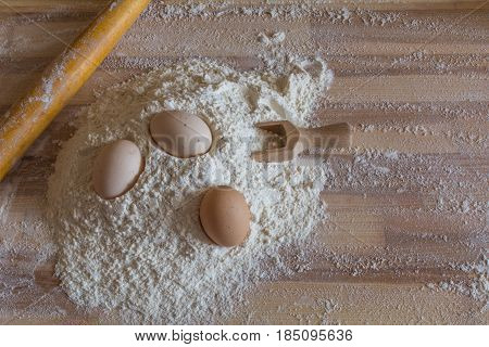 Bakery Background. Flour, Domestic Eggs, Wooden Spoon For Flour And A Wooden Rolling Pin