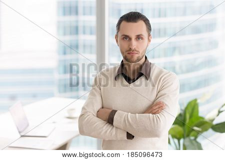 Portrait of young businessman standing in office with arms crossed. Ambitious successful entrepreneur, small business owner or company director posing looking at camera with serious facial expression