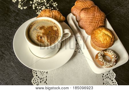 Cup of instant coffee with bagel and biscuits in white plate on white openwork napkin on black background