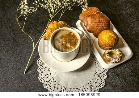 Instant coffee in  white cup with biscuits on white plate on an openwork napkin with twig of flower on black background