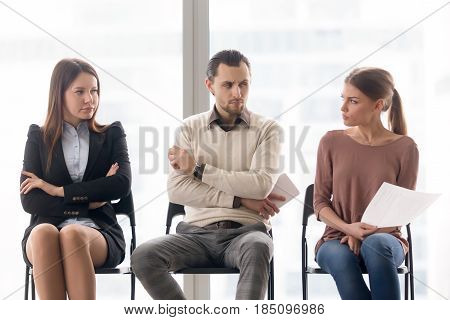 Male and female candidates waiting for interview, sitting together in a row, looking at each other with hate and dislike, feeling jealous envious, rivalry and competition while applying for a job