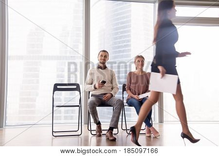Unhappy attractive businesswoman walking by male and female job candidates sitting on chairs, gazing at her and smiling, gloating over unfortunate competitor, beating rival, competing for position