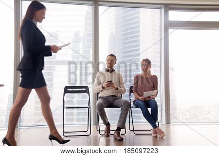Happy hired woman walking in the room, got a job, being promoted to the post while her colleagues or other applicants looking at businesswoman with envy and hate, feeling winner and loser