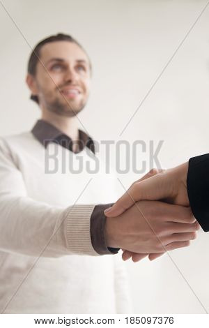 First meeting with client and business acquaintance, confident handsome young happy man and woman shaking hands, greeting handshake before negotiations, partnership, working relations. Focus on hands