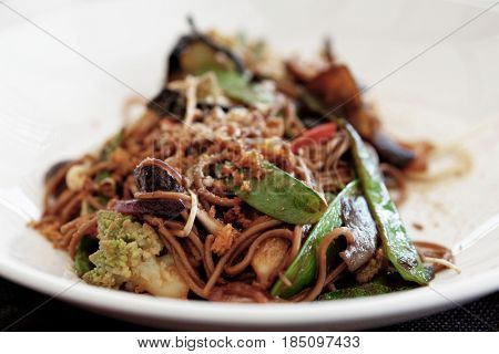 Buckwheat noodles with vegetables and mushrooms, Asian style dish on white plate, toned image