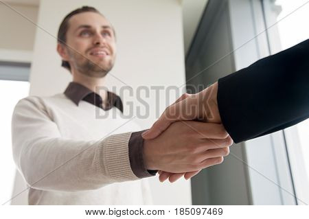 Close up view of young cheerful businessman shaking female hand, business partners binding agreement with a friendly handshake while standing indoors, successful effective negotiations, sealing deal