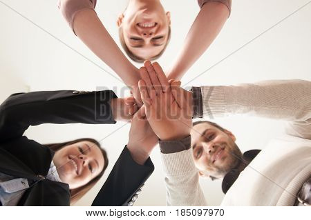 Bottom view of hands put together, looking down at camera, team of happy smiling entrepreneurs united by common project, team building activity, achieve success together, successful business plan