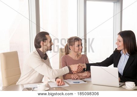Young friendly businesswoman shaking hands with business partners during meeting sitting at office desk. Executive and employees handshaking starting briefing, work results report, nice to meet you