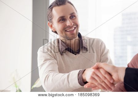 Portrait of cheerful handsome young businessman shaking female hand on meeting, nice to meet you, business partners making successful deal, hiring professional, getting acquainted with new colleague