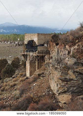 The old remaining concrete tower that is crumbling for the dam at Tumalo Reservoir alongside rich cut layers of rock on a winter day in Central Oregon.