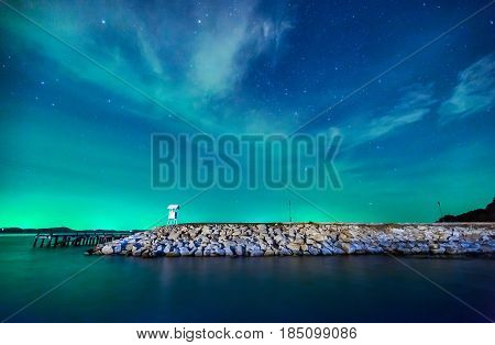 Beautiful calmness starry night sky with cloudy and colorful light at seashore pier of Khao Laem Ya National Park Rayong province eastern Thailand