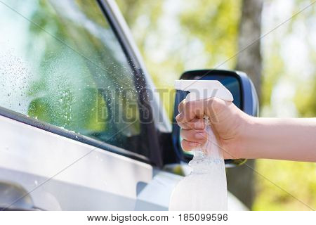 Washes The Window Of The Car.