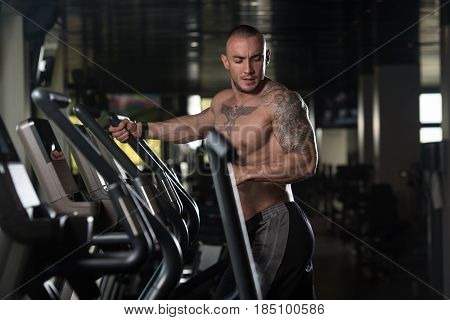 Young Man Doing Aerobics Elliptical Walker In Gym
