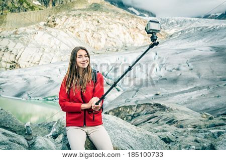 Young Woman Hiking in the Swiss Alps, Taking a Selfie. This is a generic, low-cost camera and not the 'famous original' brand.