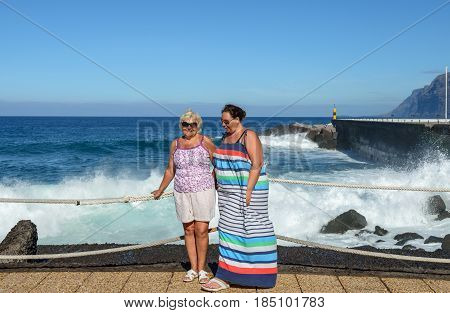 Two tanned women in bright clothes are standing on embankment in sunlight on bright blue water and sky and splashing wave background.