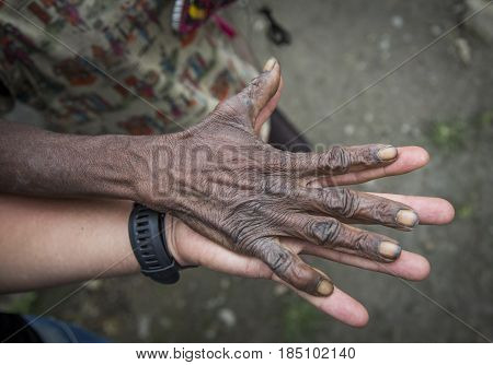 young of a white young man holding a hand of old papuan lady