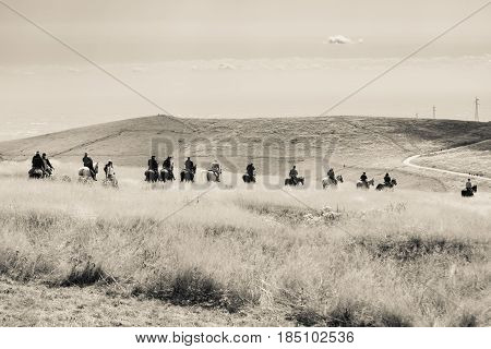 Horsemen proceed in single file through high grass of a hilly landscape.