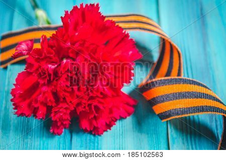 Red Carnations Tied With Saint George Ribbon On Gray
