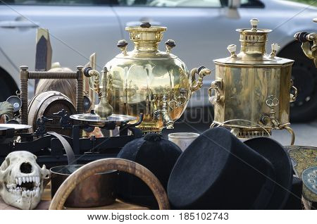In the nature on the background of the car antique utensils for making tea and hats in the form of a hatch